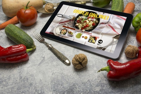 A tablet demonstrating mobile ordering of meal delivery, surrounded by fresh produce and a fork