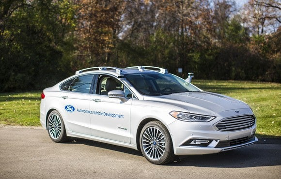 A white 2017 Ford Fusion with self-driving sensors visible, parked near a wooded field.