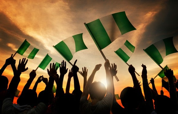 Group of people waving the Nigerian flag as the sun sets in the distance.