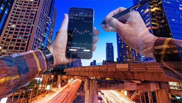 A man checks his stock portfolio on a smartphone.