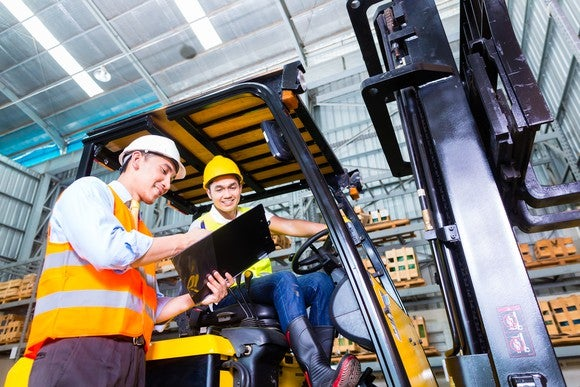 A man operating a forklift and talking with his supervisor.