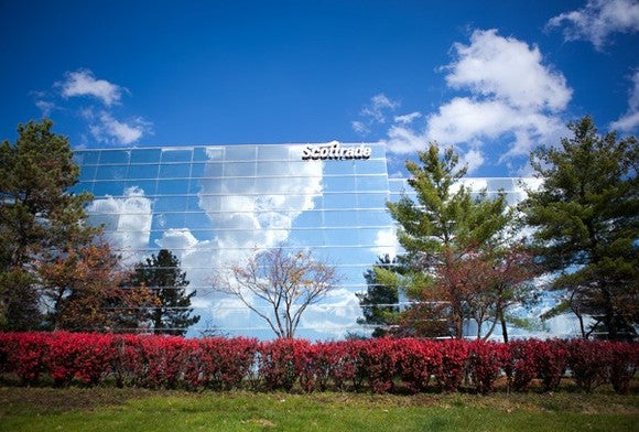 Scottrade office; glass building set behind trees and bushes.