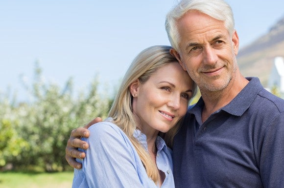 An older couple stands smiling outdoors, with the man's arm around the woman's shoulder.