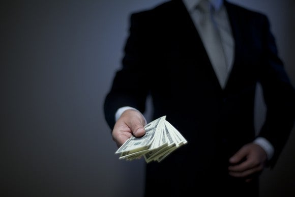 A person in a suit handing over a stack of cash.