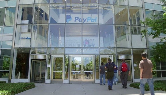 Glass paneled front building entrance with PayPal logo above door.