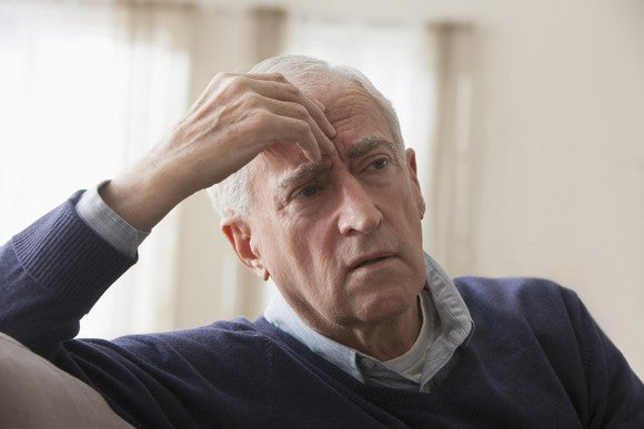 A worried senior citizen puts his hand to his forehead as he gives a concerned expression.