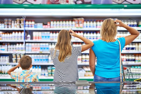 A family of shoppers scratch their heads in confusion as they look over the grocery store selections.