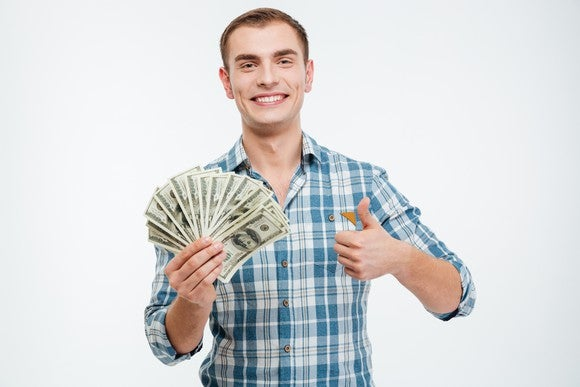 happy man holding fanned out bills in one hand and making thumbs-up gesture with other hand