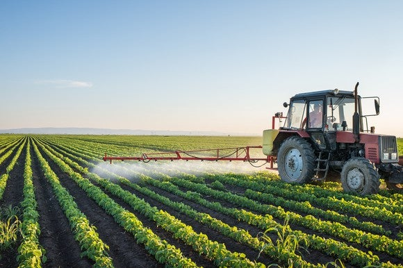 A farmer using a tractor to spray his crop with an insect repellent.