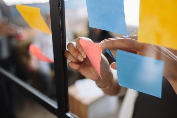A woman sticking Post-It notes on her wall.