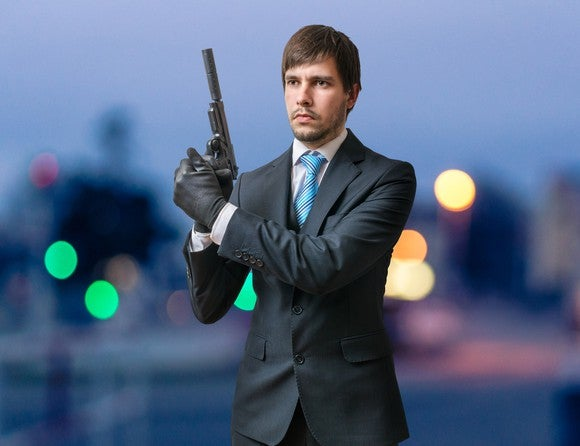 Man in suit holding pistol with silencer