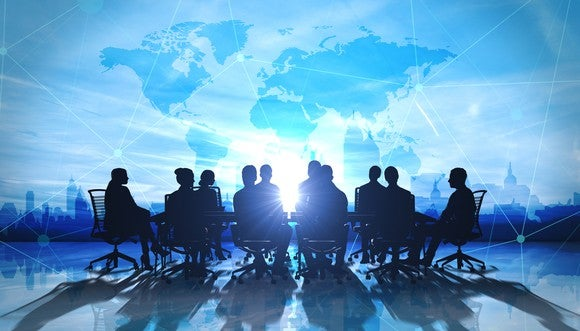 Business meeting taking place in front of a map of the world
