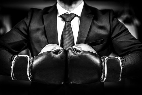 A businessman wearing boxing gloves. The photo is in black and white.