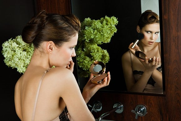 Young woman applying blush in mirror.