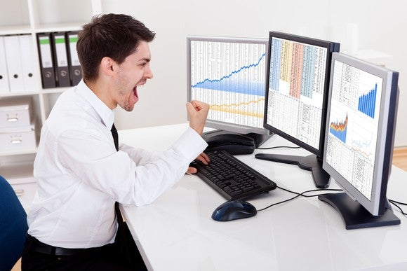 An investor cheering on big portfolio gains in front of three computer screens.
