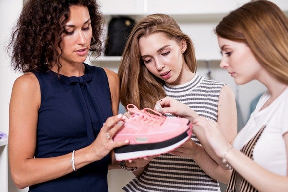 Three women examine a pair of sneakers.
