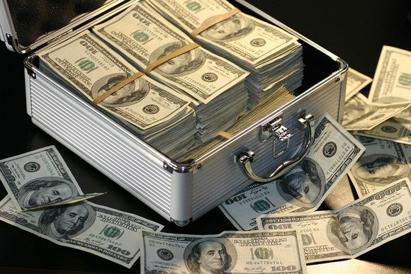 A silver suitcase with bundled $100 bills.