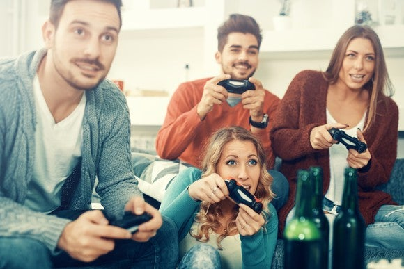 Four friends, two men and two women, holding game controllers with excitement in their faces.