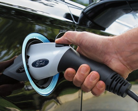 A close-up of a Ford-branded electric-vehicle charger plugged into a 2017 Ford Fusion Energi plug-in hybrid sedan.