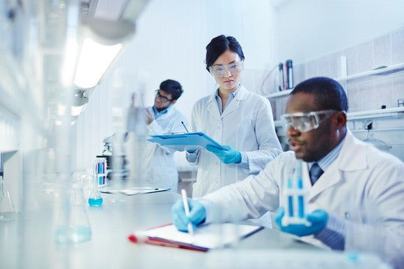 Three people in white lab coats and safety glasses in a lab.