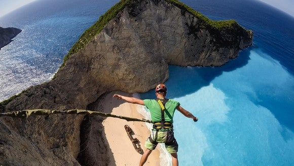 Guy in harness and helmet attached to a bungee chord high above a beautiful view of a clear blue ocean and a rock island.