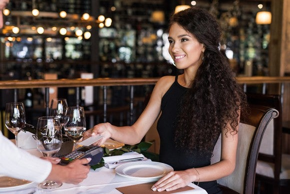 Woman using card to pay for a meal at a restaurant