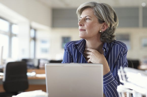 mature woman using laptop looking out the window