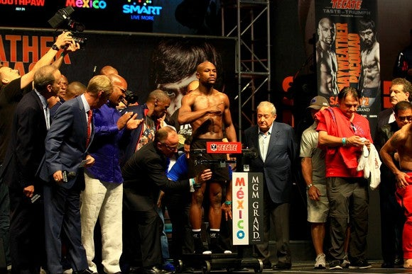 Floyd Mayweather standing on a scale for a weigh in, surrounded by people.
