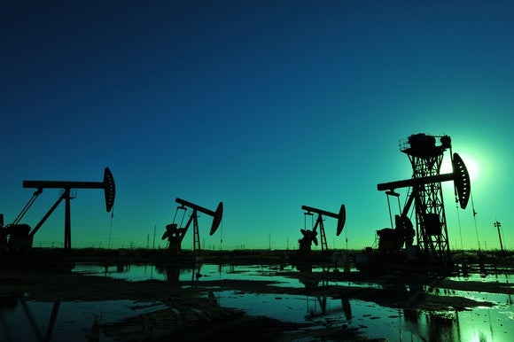Oil pumps in silhouette against a dark sky.