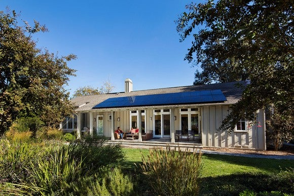 Rooftop solar system on a single level home with trees around the house.