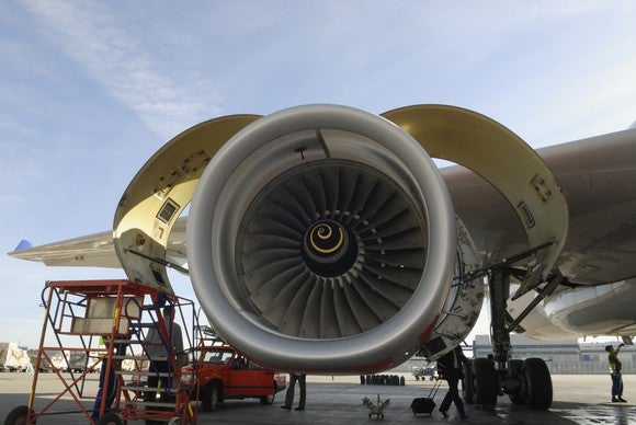 A jet engine being inspected on a tarmac.