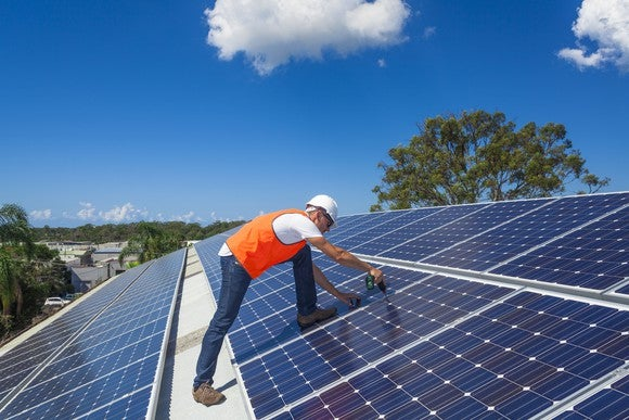 A technician on a roof securing solar panels to it.