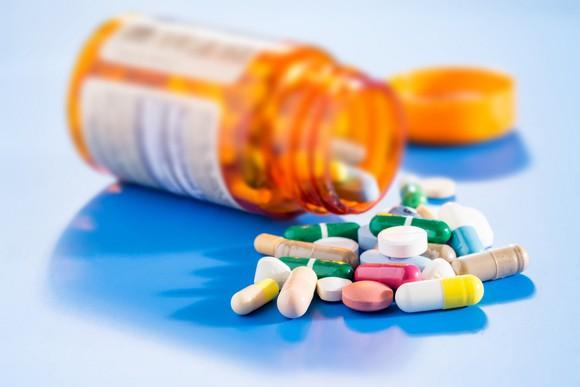 Pill bottle spilling an assortment of pills on a blue counter.