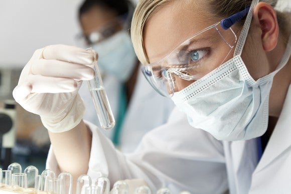 A biotech lab researcher holding and examining liquid in a test tube.
