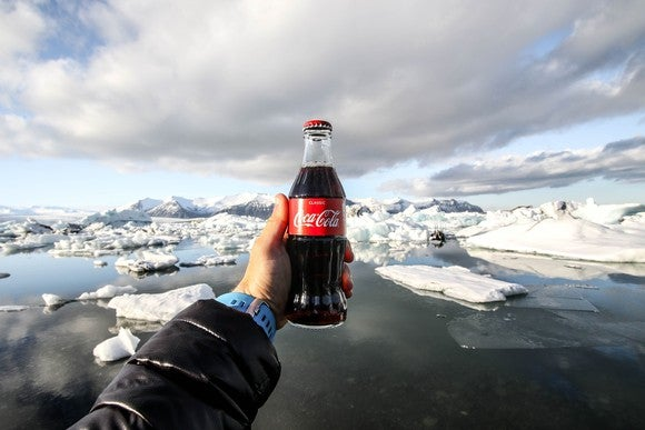 A hand holds a bottle of Coca-Cola backed up by a glacier vista.