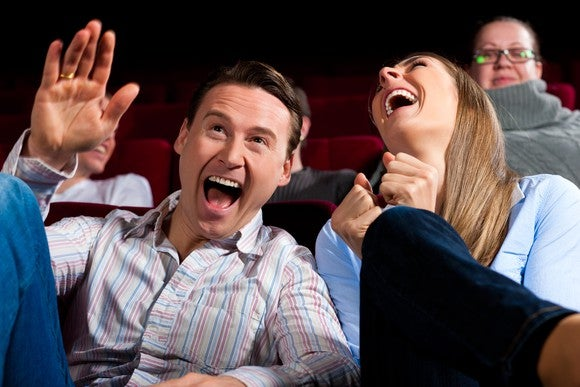 Middle-aged man and woman sitting in a theater and laughing hard, suggesting they're watching a funny scene in a movie. A few other people are visible in seats behind them.