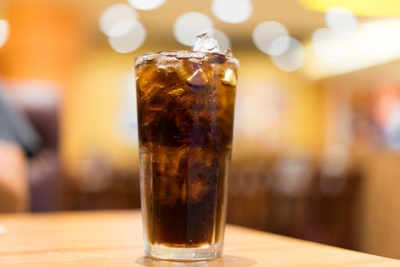 """Glass of Coke with ice on wooden table, with background """"bokeh"""" soft lighting effect."""