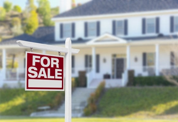 A For Sale sign in front of a house.