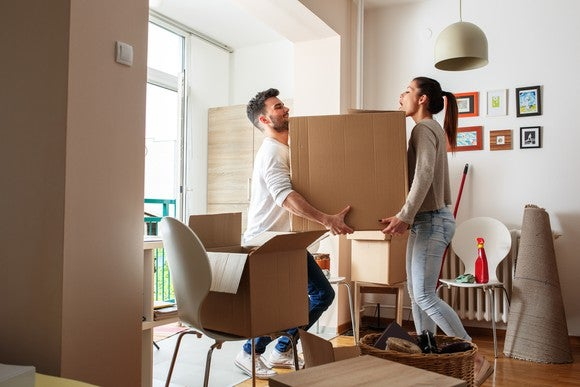 young man and woman carrying a large cardboard box through a house