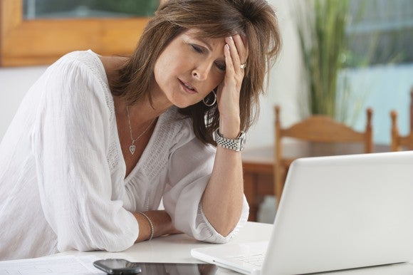 A frustrated woman holds her head as she sits in front of her laptop.