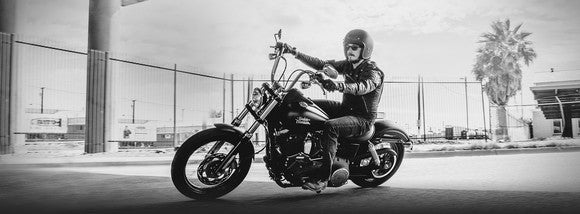 black-and-white photo of man riding a Harley-Davidson Dyna motorcycle