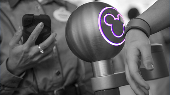 A guest wearing a MagicBand triggers an entrance turnstile at a Disney World park.