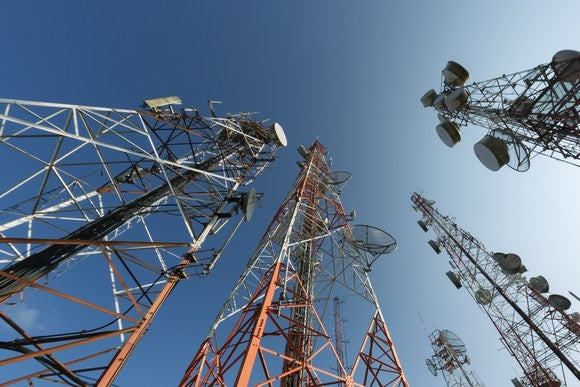 A group of telecom towers, looking up from the ground.