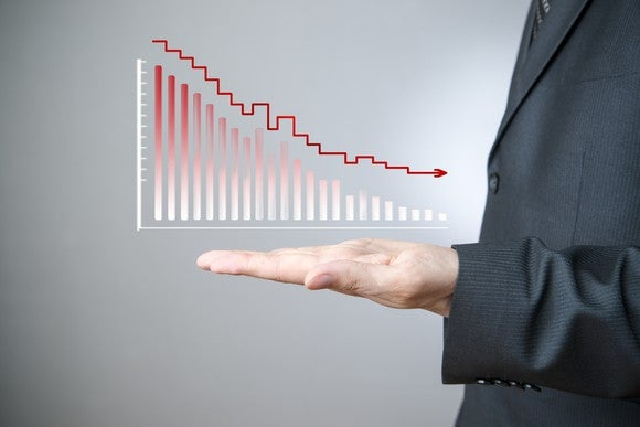 A business man holding out his flat hand, which has a bar chart showing declines on it.