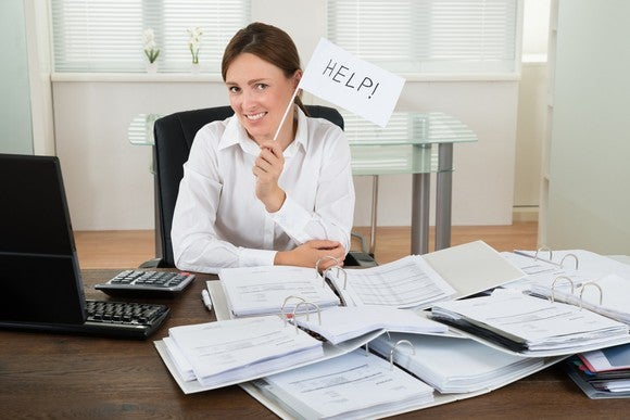 """Smiling woman at desk covered with paper, holding up small """"help"""" sign."""