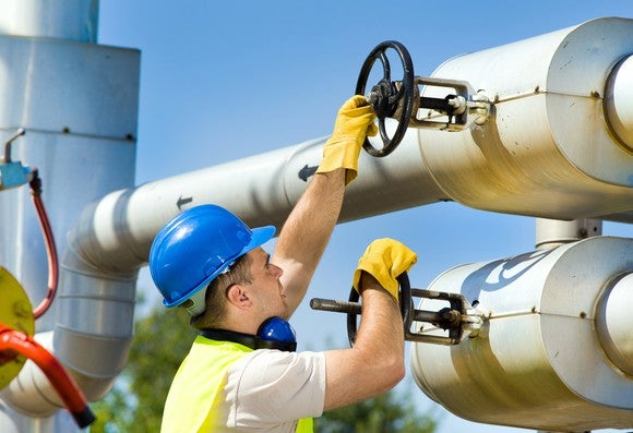 A man in a hard hat turning valves on a pipeline