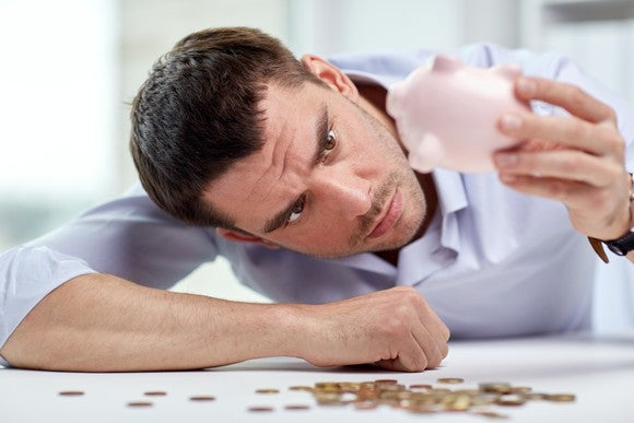A man emptying his piggy bank and finding very little cash.