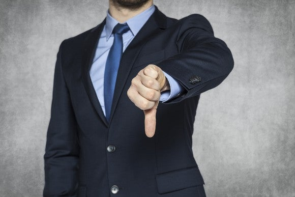 A man in a business suit giving the thumbs-down sign.