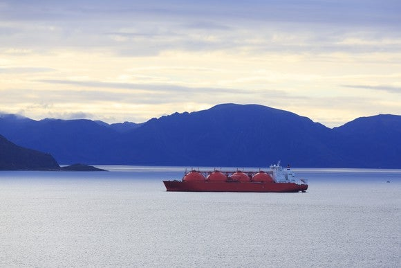 An oil tanker in Alaskan waters. Mountains are in the background.