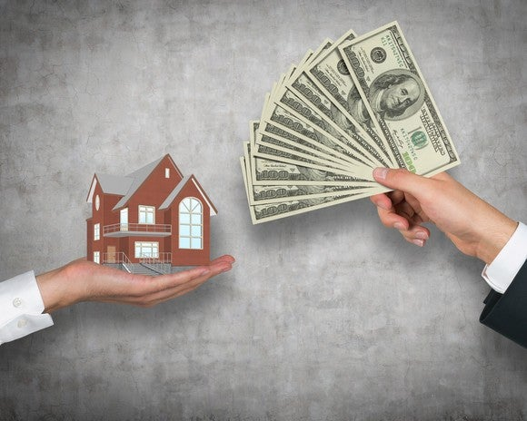 A hand holding up money in return for a miniature house